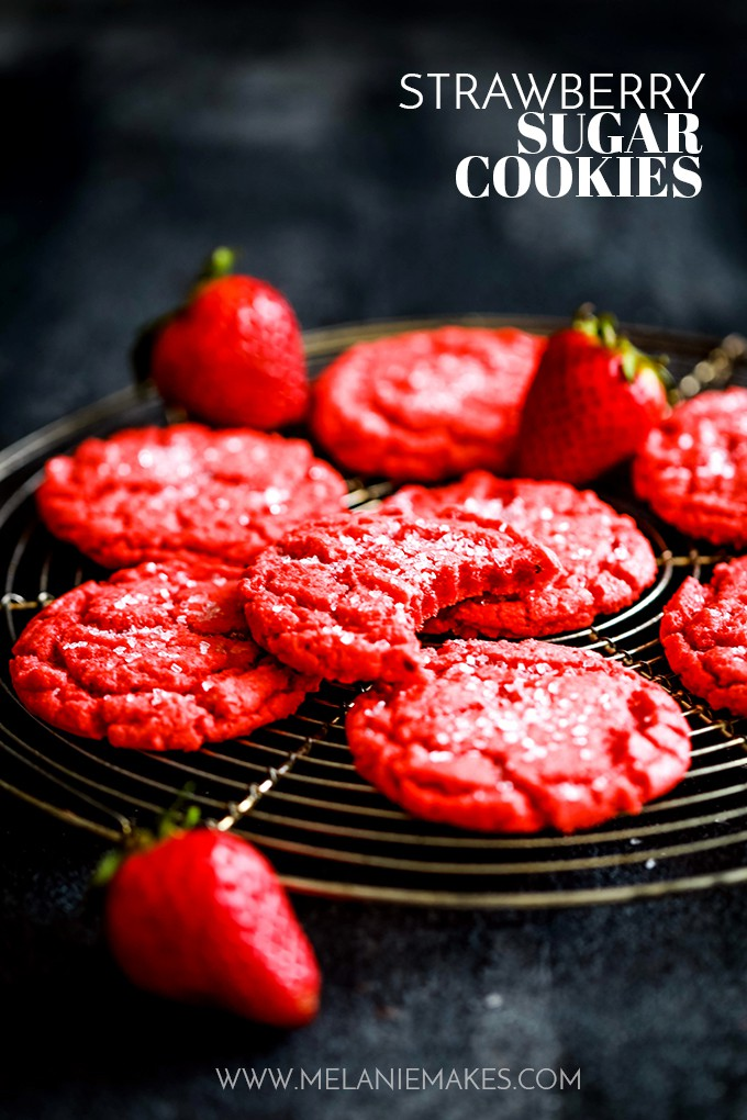 Strawberry Sugar Cookies rest on a cooling rack with three strawberries.