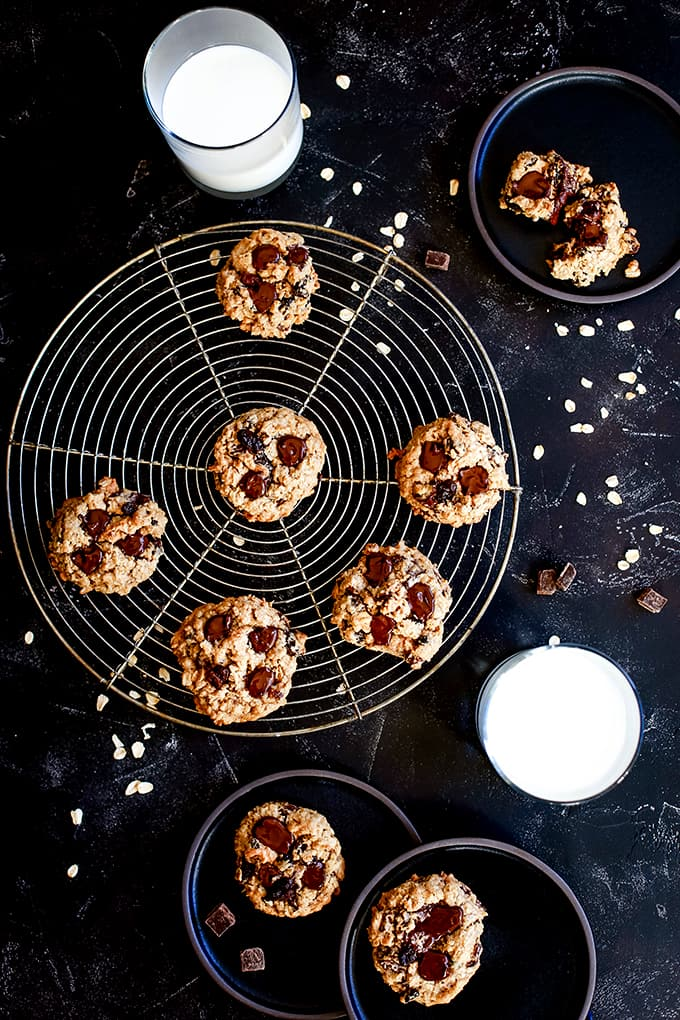 Oatmeal Raisin Chocolate Chip Cookies on a circular cooling rack and black plates with two glasses of milk.