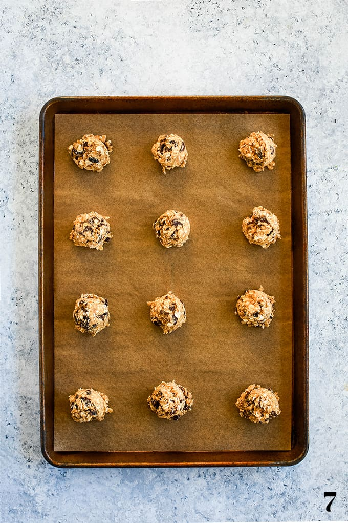 Balls of Oatmeal Raisin Chocolate Chip dough on a parchment lined baking sheet.