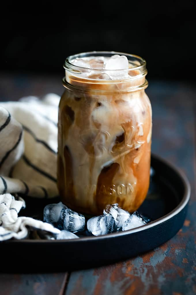 Milk swirls in a glass of iced coffee resting on a black tray with ice.
