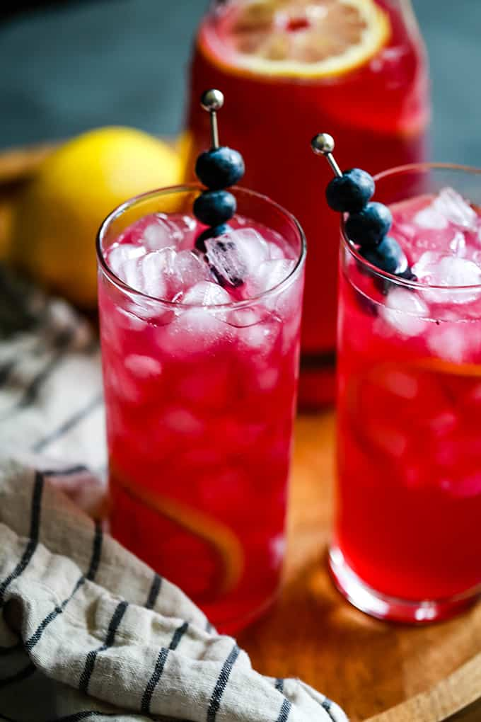 Two glasses of Blueberry Lemonade sit on a wooden tray flanked by a striped napkin.