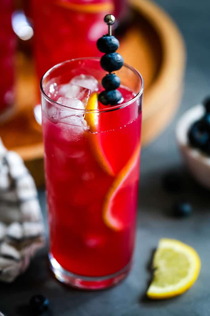 A glass of Blueberry Lemonade garnished with fresh blueberries and lemon slices.