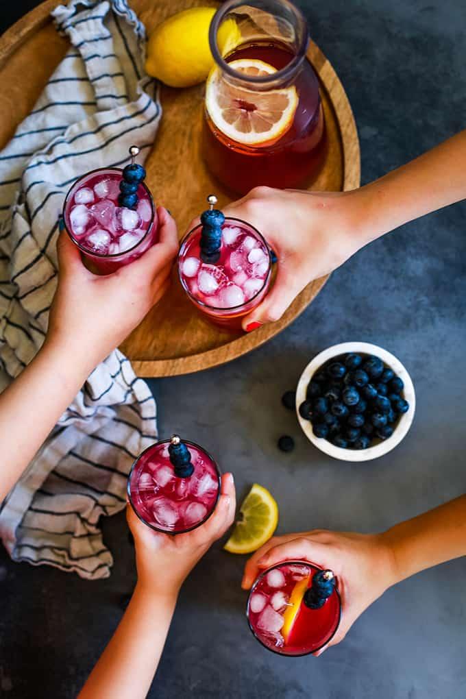 Four hands reach for glasses of Blueberry Lemonade.