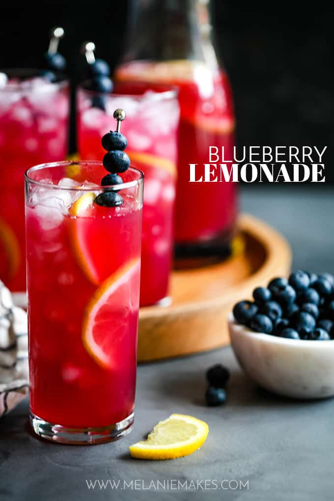 A glass of Blueberry Lemonade sits next to a bowl of blueberries and a lemon slice in front of a tray with other glasses.