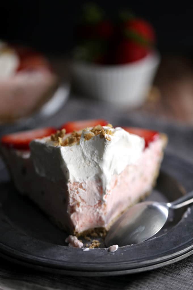 This Strawberry Cheesecake Ice Cream Pie takes just 10 minutes and five ingredients to prepare! Strawberry cheesecake ice cream is swirled together with cheesecake pudding and whipped topping before being poured into a graham cracker pie shell. It's then frozen before being garnished with slices of juicy strawberries, a pillowy cloud of additional whipped topping and a dusting of graham cracker crumbs.