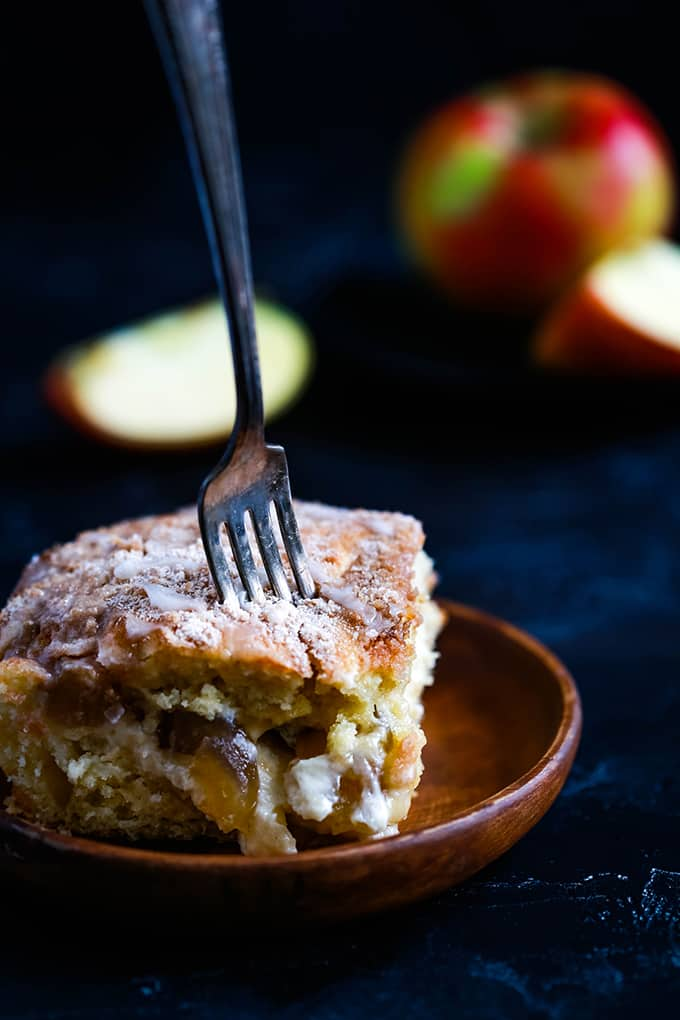 A slice of Caramel Apple Cheesecake Coffee Cake on a wooden plate with a fork piercing the top. Cut apples sit in the background.