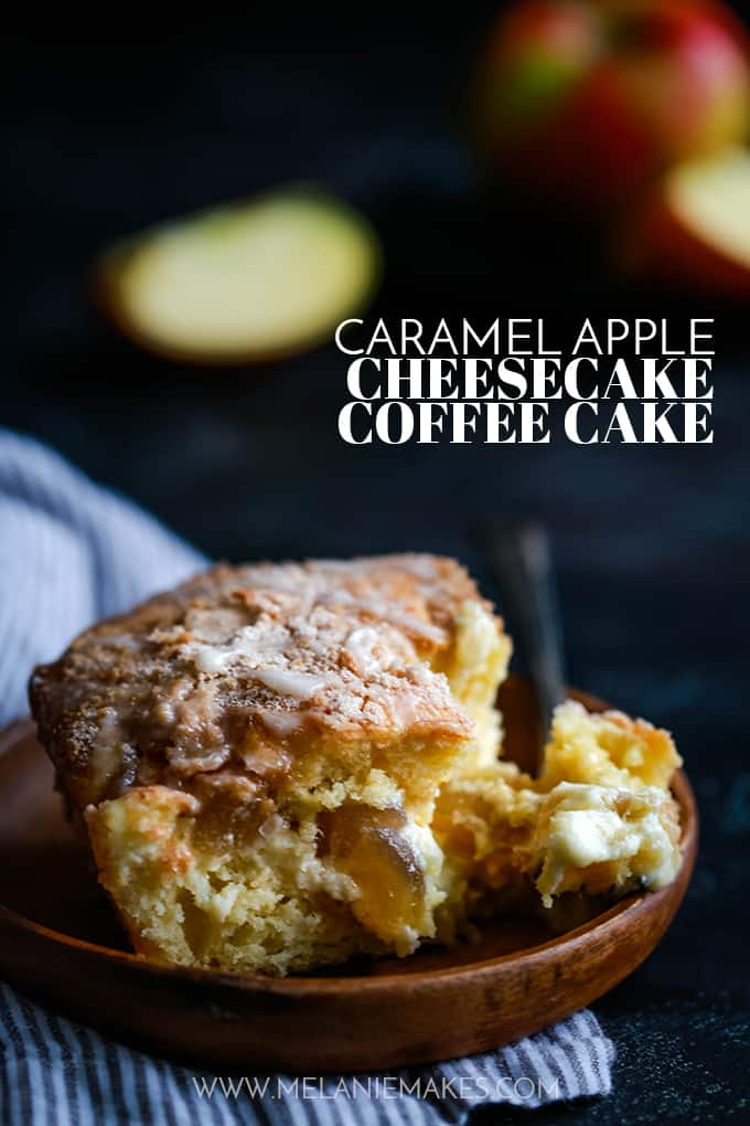 A slice of Caramel Apple Cheesecake Coffee Cake on a wooden plate sits on a striped napkin with apples in the background.