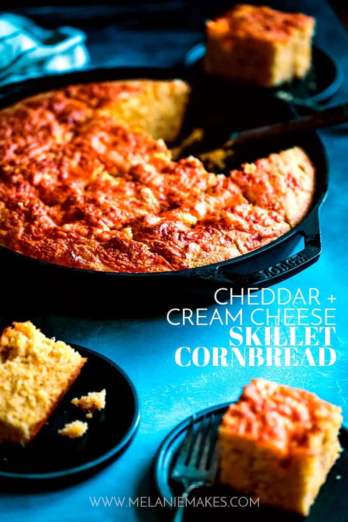 Three black plates with pieces of Cheddar and Cream Cheese Skillet Cornbread surround a cast iron skillet.