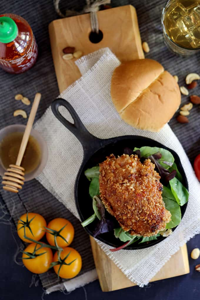 This seven ingredient Honey Sriracha Nut Oven Fried Chicken says so long to spattering oil and instead gets it's crispy crunch from an oven. Marinated in buttermilk and coated in panko bread crumbs and mixed nutsbefore beingbathed in a delicious honey Sriracha sauce, thischicken is the definition of sweet heat.