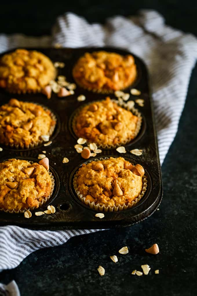 A muffin tin of Pumpkin Butterscotch Oatmeal Muffins sits on a striped napkin on a dark background.