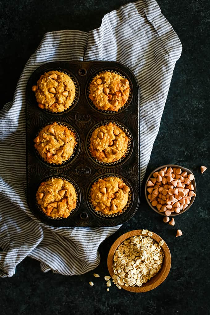 A muffin tin of Pumpkin Butterscotch Oatmeal Muffins sits on a striped napkin on a dark background with a small wooden bowl of dry oatmeal and a smaller bowl of butterscotch chips.
