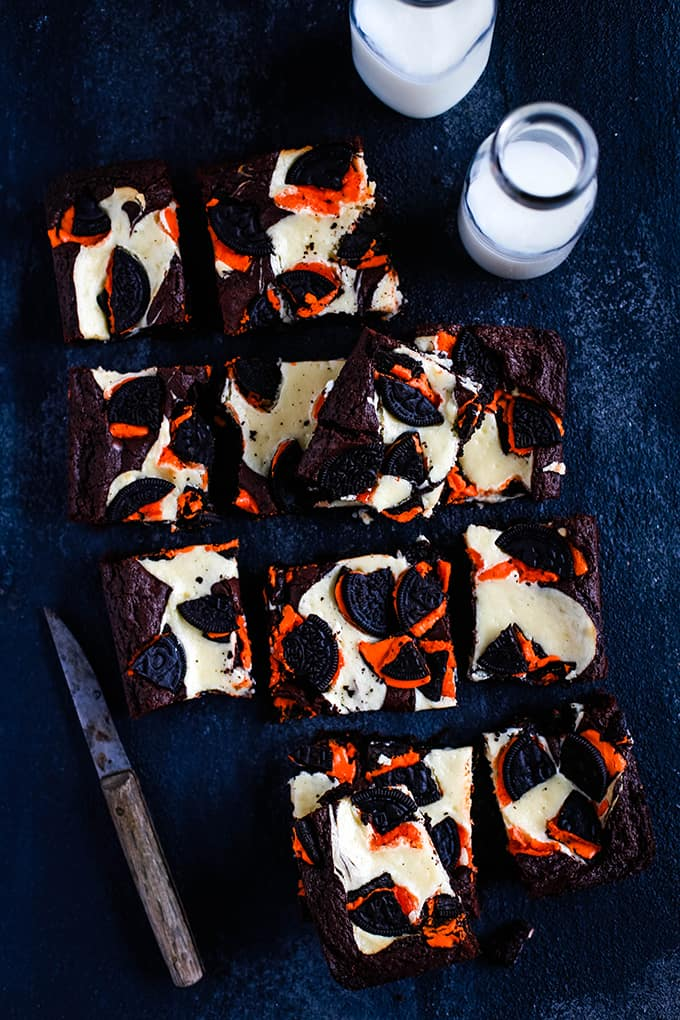 Squares of Oreo Cheesecake Brownies sits on a black background along with a knife and two bottles of milk.