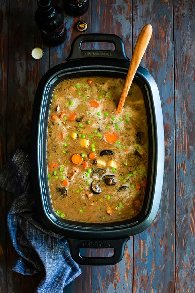 A slow cooker filled with Slow Cooker Beef and Guinness Pot Pie Soup with a wooden spoon.