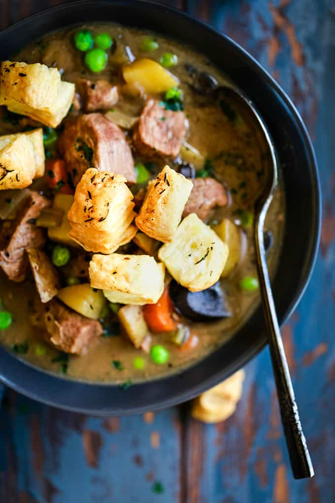 An overhead view of a bowl of Slow Cooker Beef and Guinness Pot Pie Soup with Thyme Puff Pastry Croutons with a spoon.