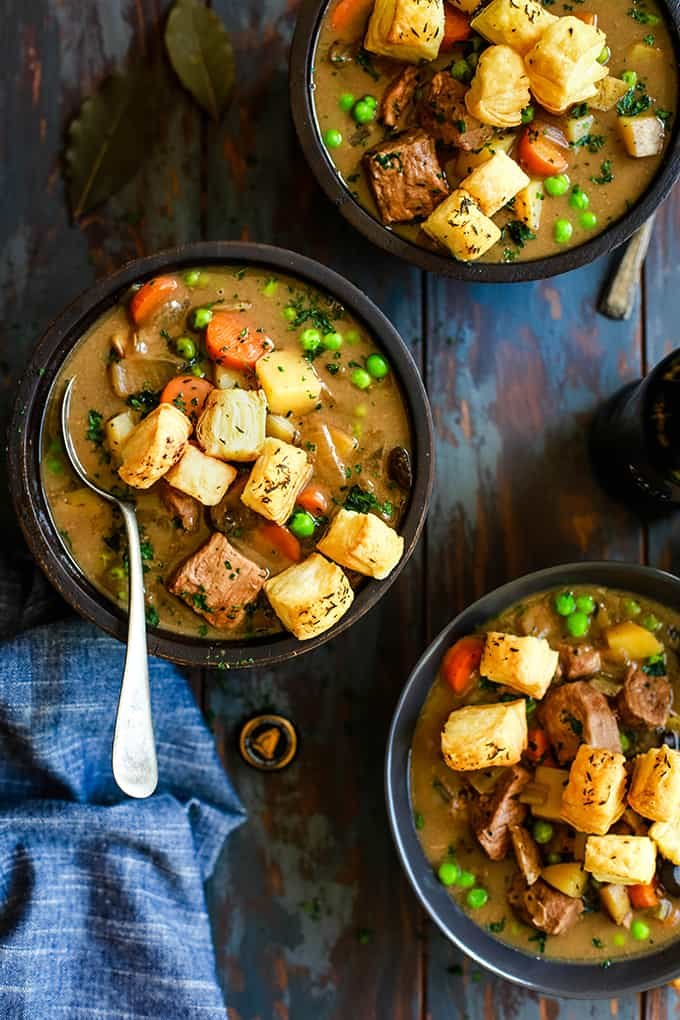 Three bowls of Slow Cooker Beef and Guinness Pot Pie Soup with Thyme Puff Pastry Croutons.