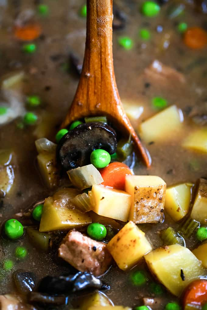 A wooden spoon in a bowl of Slow Cooker Beef and Guinness Pot Pie Soup.