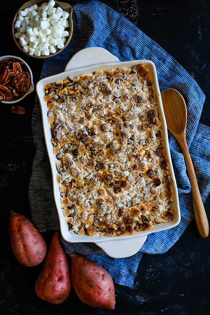 An overhead view of a casserole dish of Make Ahead Sweet Potato Casserole sits on a striped napkin surrounded by a wooden spoon, three sweet potatoes, a bowl of mini marshmallows and a bowl of pecans.
