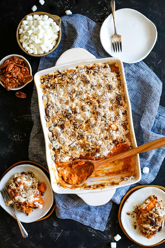 An overhead view of Make Ahead Sweet Potato Casserole with a wooden spoon surrounded by three white plates, pecans and marshmallows.