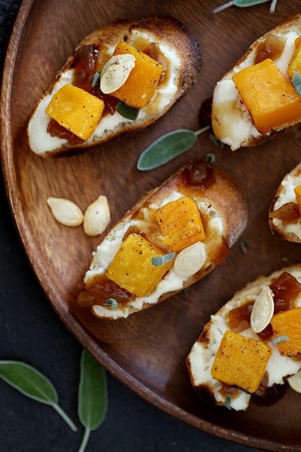 These Roasted Butternut Squash Bruschetta are not only easy on the eyes but they're also equally easy to assemble. Toasted bread slices are topped with a layer of ricotta cheese and then drizzled with balsamic caramelized onions before being studded with roasted butternut squash and sprinkled with fresh sage and toasted squash seeds.