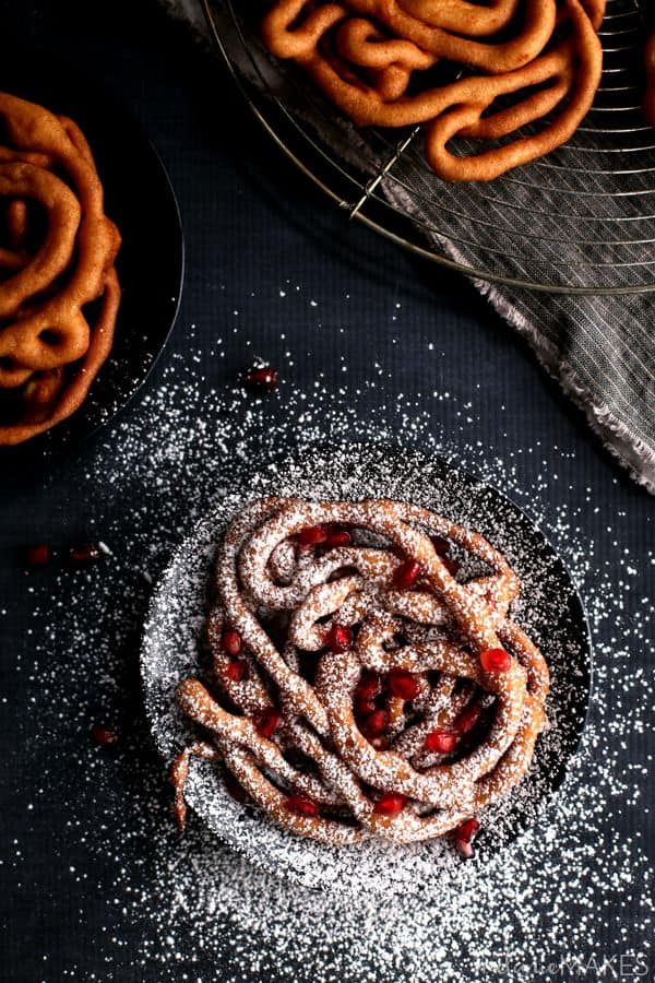 These Mini Eggnog Funnel Cakes are sure to be the star of any holiday party or gathering. A cinnamon eggnog batter is fried into a web of interlacing circles before being topped by a snow shower of powdered sugar and studded with pomegranate arils (seeds) for the perfect pop of holiday color.