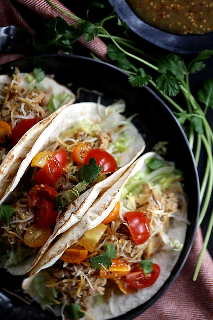 These Slow Cooker Honey Mustard Pork Tacos with Candied Bacon couldn't be easier, yet more flavorful.  Just four ingredients are added to the slow cooker and the sweet and tangy pork that emerges is stuffed into tortillas with candied bacon, lettuce, cheese and tomatoes.  Your new favorite taco awaits!