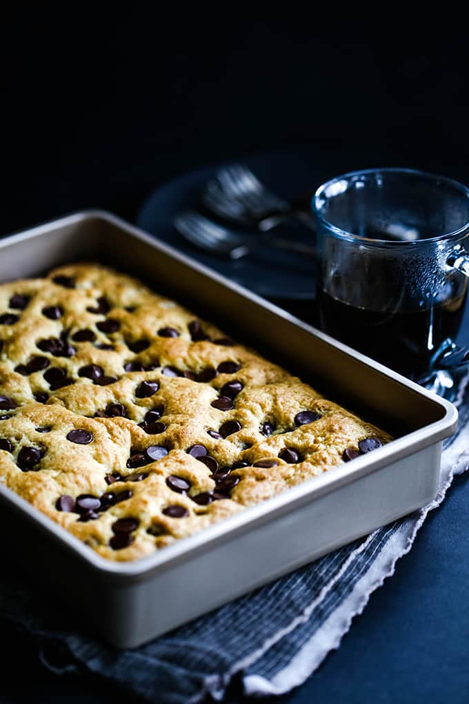A pan of Chocolate chip Sour Cream Coffee Cake sits on a striped napkin with a cup of coffee.
