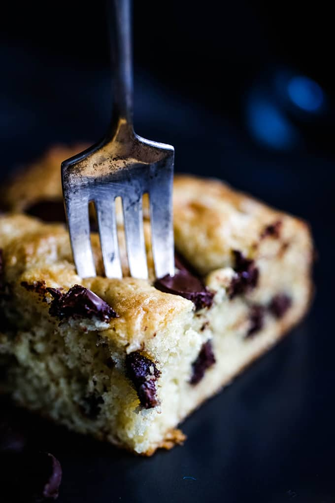 A fork inserted into a piece of Chocolate Chip Sour Cream Coffee Cake.
