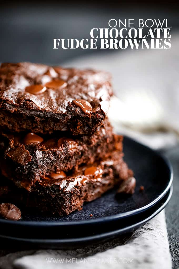 A stack of three One Bowl Chocolate Fudge Brownies sit on two black plates.
