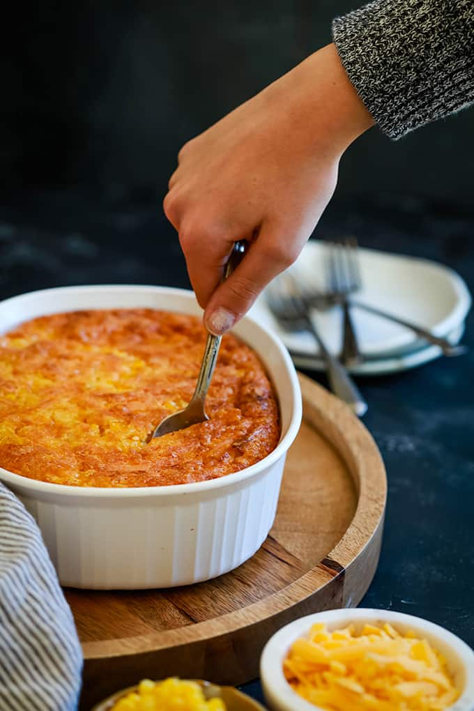 A hand inserts a spoon into a white dish of Cheesy Corn Casserole on a wooden platter, surrounded by white plates and forks and two small bowls full of cheese and corn.