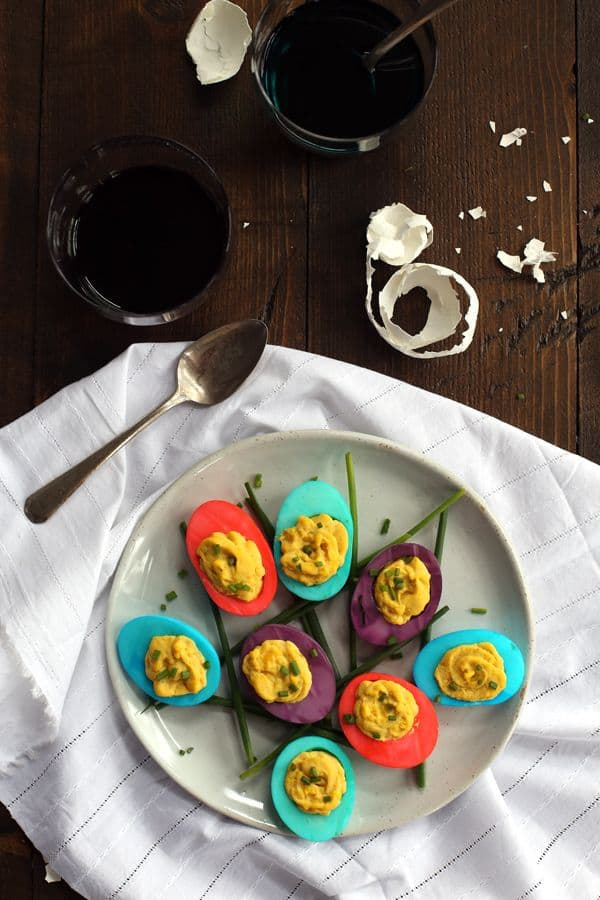 An overhead view of a plate of Dyed Deviled Eggs on a white napkin with glasses of dye.