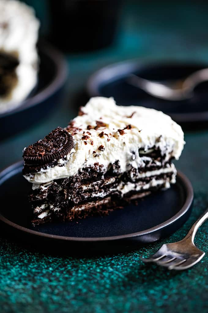 A slice of Irish Cream Oreo Icebox Cake sits on a black plate.