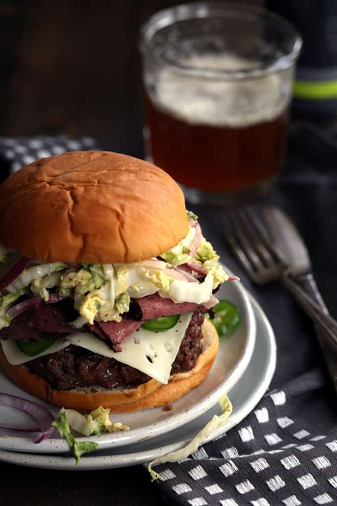 A Copycat Fat Doug Burger that you'd find at Michael Symon's B Spot restaurant. A 3/4 pound beef burger is covered with a slice of Swiss cheese, pastrami and a large heap of jalapeno slaw and it's all sandwiched between a Hawaiian hamburger bun.
