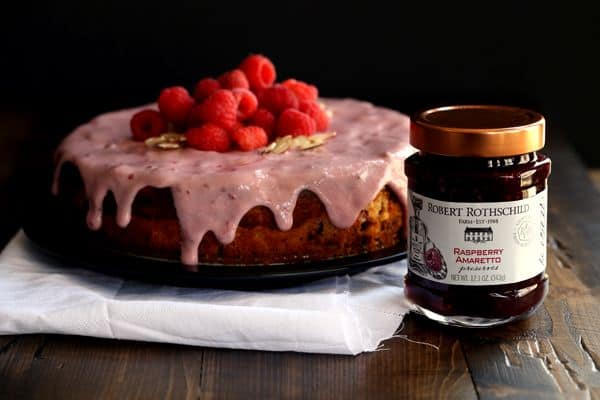 You won't believe how incredibly simple this Raspberry Almond Cheesecake Cake is to create. Layers of cake studded with fresh raspberries alternate with layers of raspberry almond cheesecake to create this amazingly delicious dessert. A raspberry almond glaze, more fresh raspberries and sliced almonds top this showstopper that's sure to impress whoever is lucky enough to snag a slice.