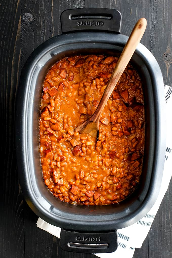 A slow cooker insert of Slow Cooker Smoky Baked Beans and a wooden spoon.