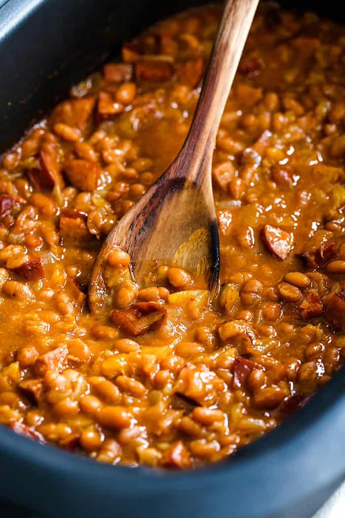 A wooden spoon rests in a slow cooker filled with Slow Cooker Smoky Baked Beans.