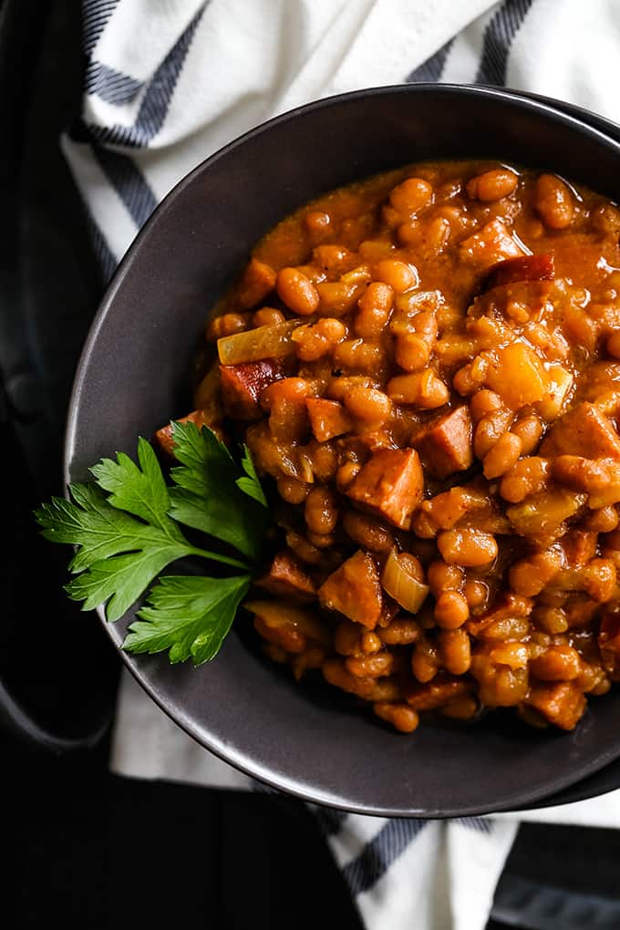 A bowl of Slow Cooker Smoky Baked Beans garnished with a sprig of parsley.