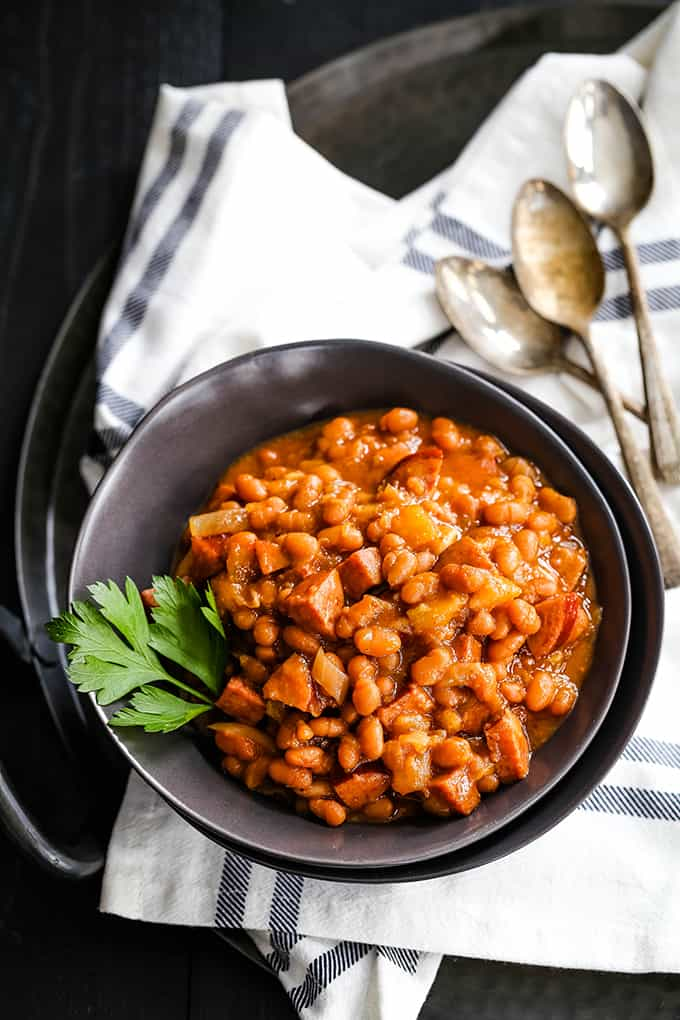 An overhead view of a bowl of Slow Cooker Smoky Baked Beans flanked by three spoons.