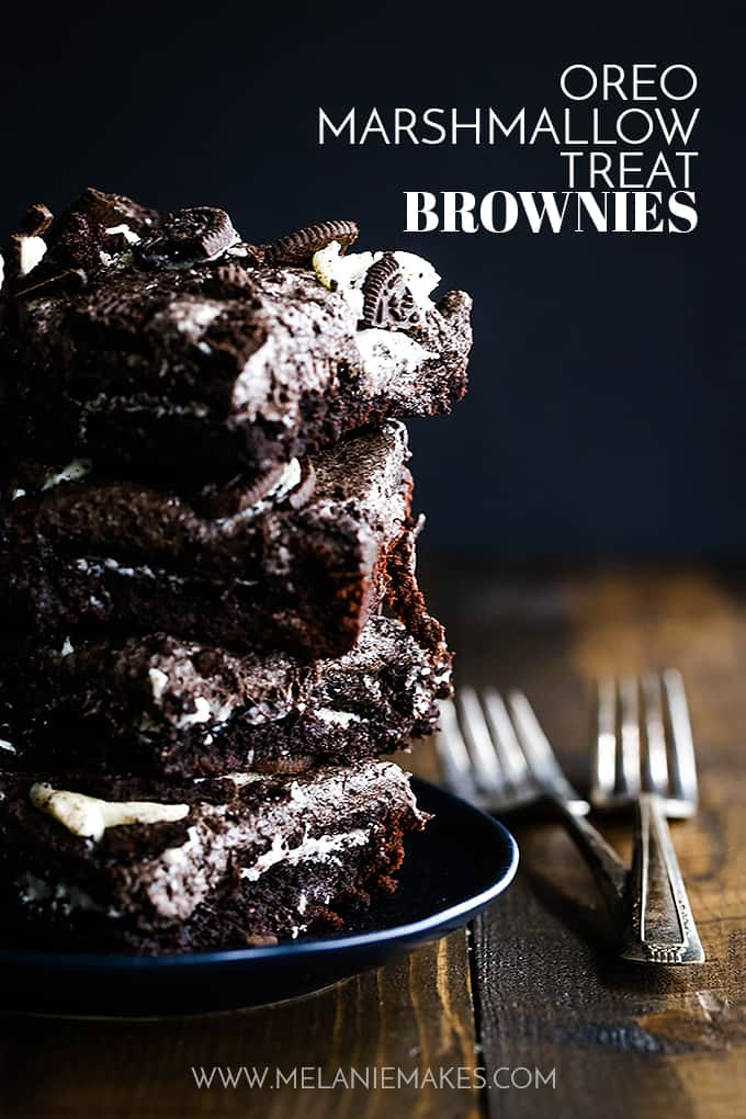 A stack of Oreo Marshmallow Treat Brownies on a black plate with two forks.