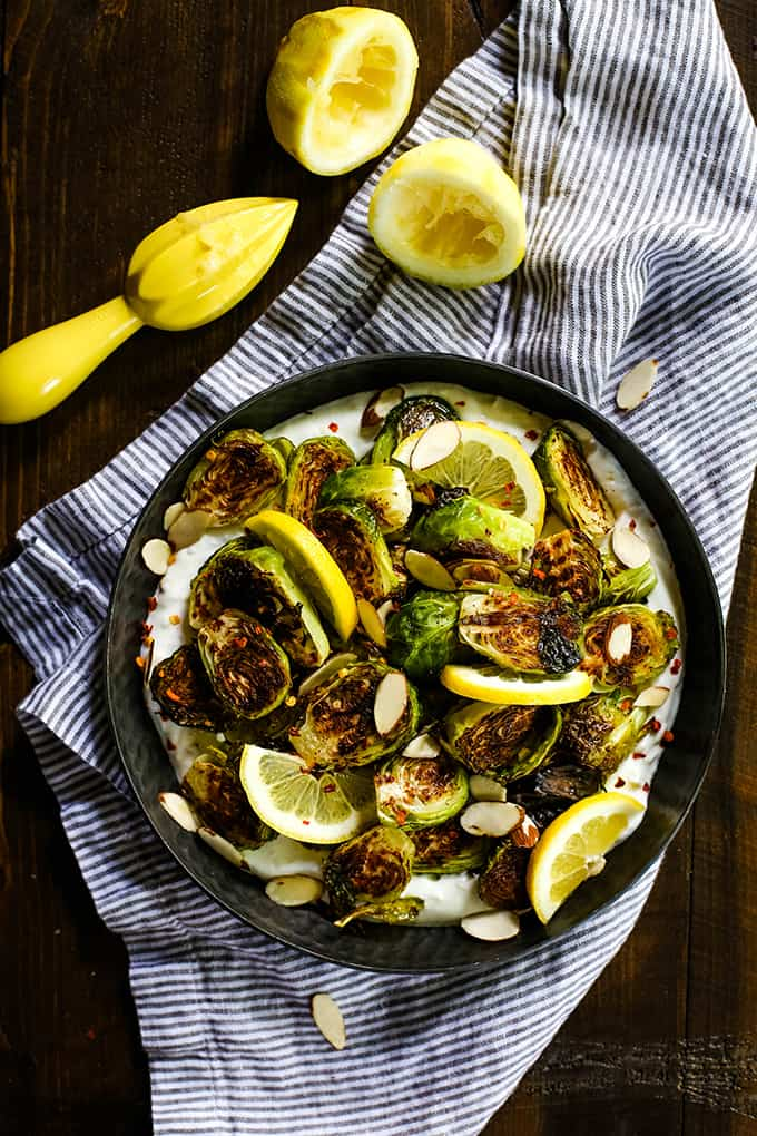 A bowl of Roasted Brussels Sprouts with Lemon and Greek Yogurt on a striped napkin flanked by two halves of a lemon.