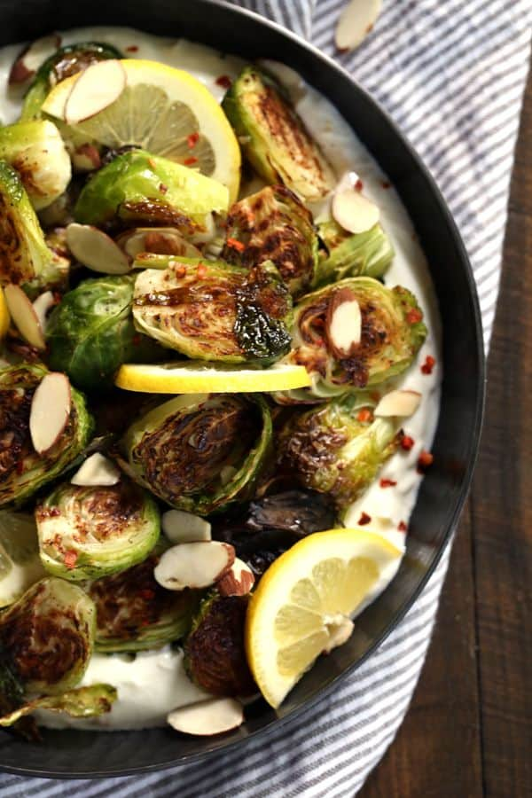 Look no further for the perfect Spring side dish, these Roasted Brussels Sprouts with Lemon and Greek Yogurt have it all. Roasted Brussels sprouts are laid on a bed of Greek yogurt spiked with lemon and sprinkled with red pepper flakes before being garnished with toasted almonds.