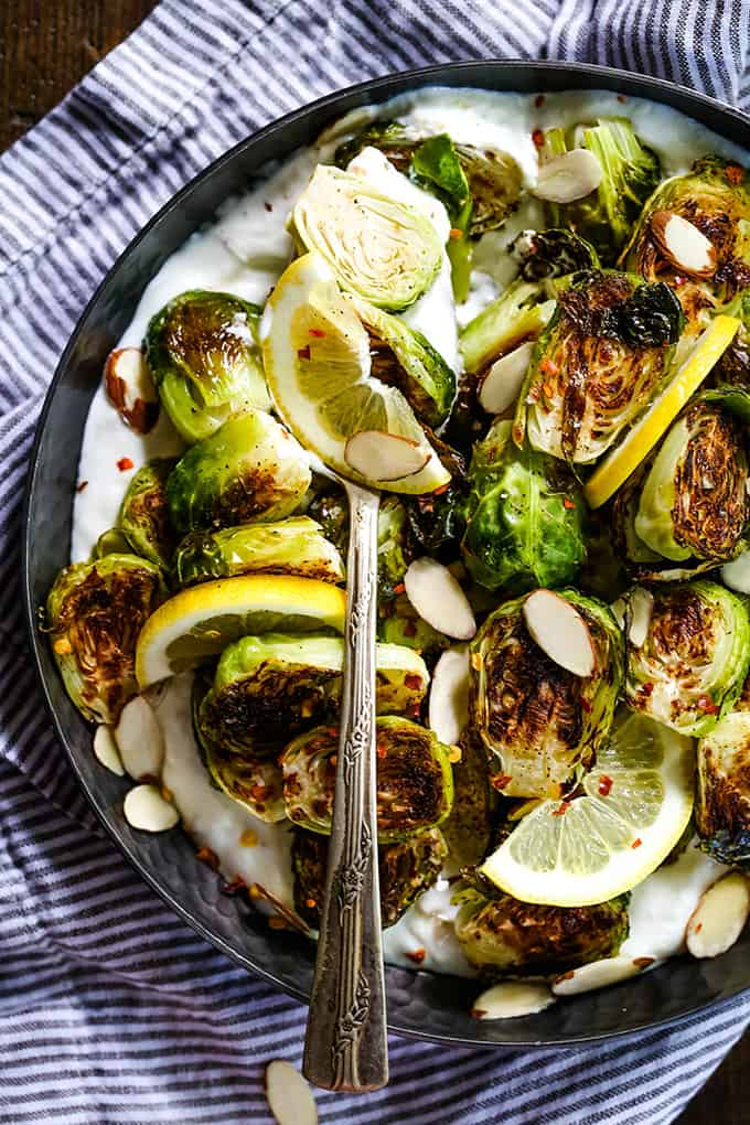 A serving spoon rests in a bowl of Roasted Brussels Sprouts with Lemon and Greek Yogurt.