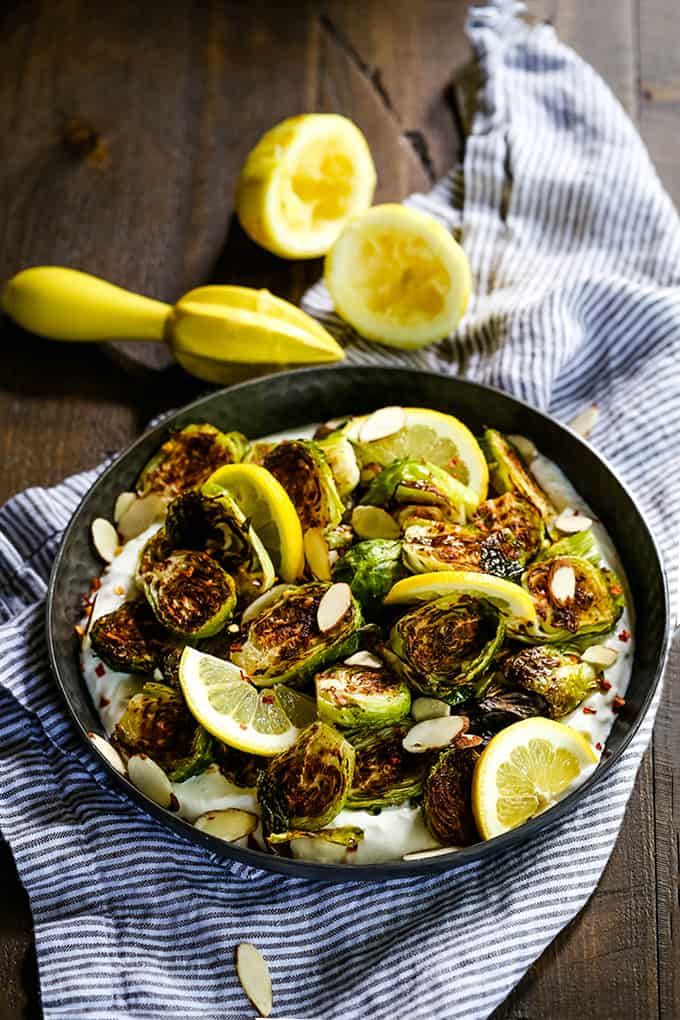 A bowl of Roasted Brussels Sprouts with Lemon and Greek Yogurt sits in front of two halves of lemon and a citrus reamer.