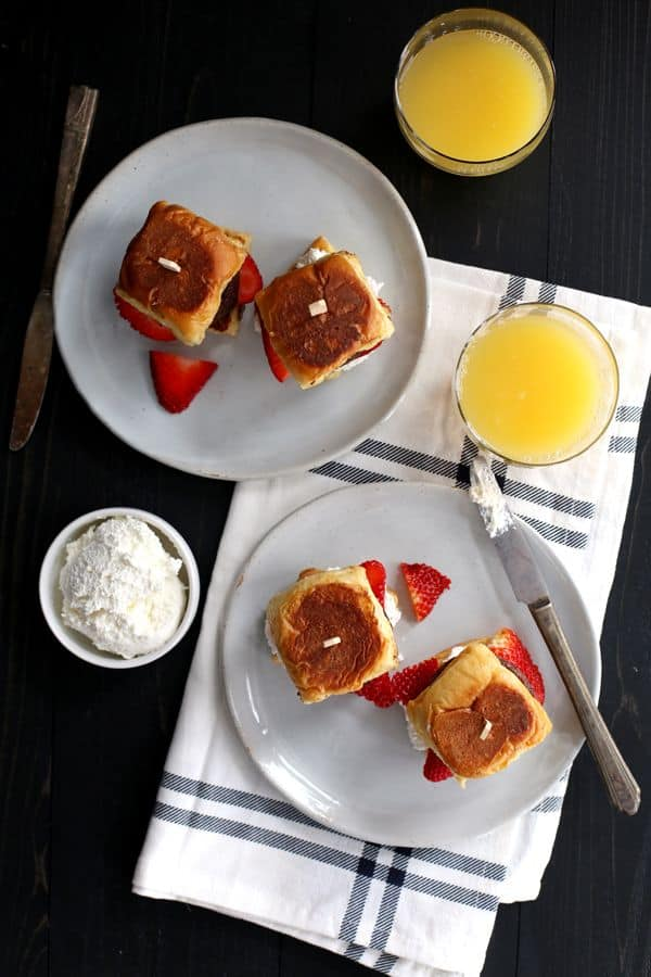 These Stuffed French Toast and Sausage Sliders are the answer to feed a crowd breakfast or brunch in a snap! Hawaiian rolls, whipped cream cheese, fresh strawberries and sausage are layered together to create the most perfectly portable French toast.