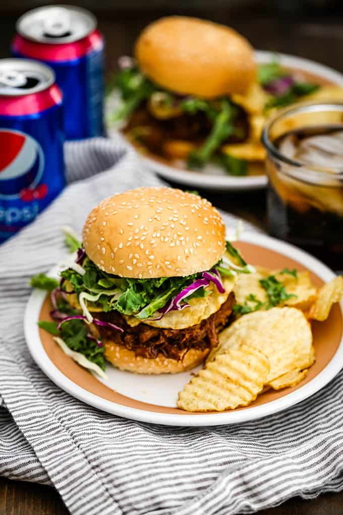 Two Slow Cooker Cherry Cola Pulled Pork Sandwiches are surrounded by cans of soda.