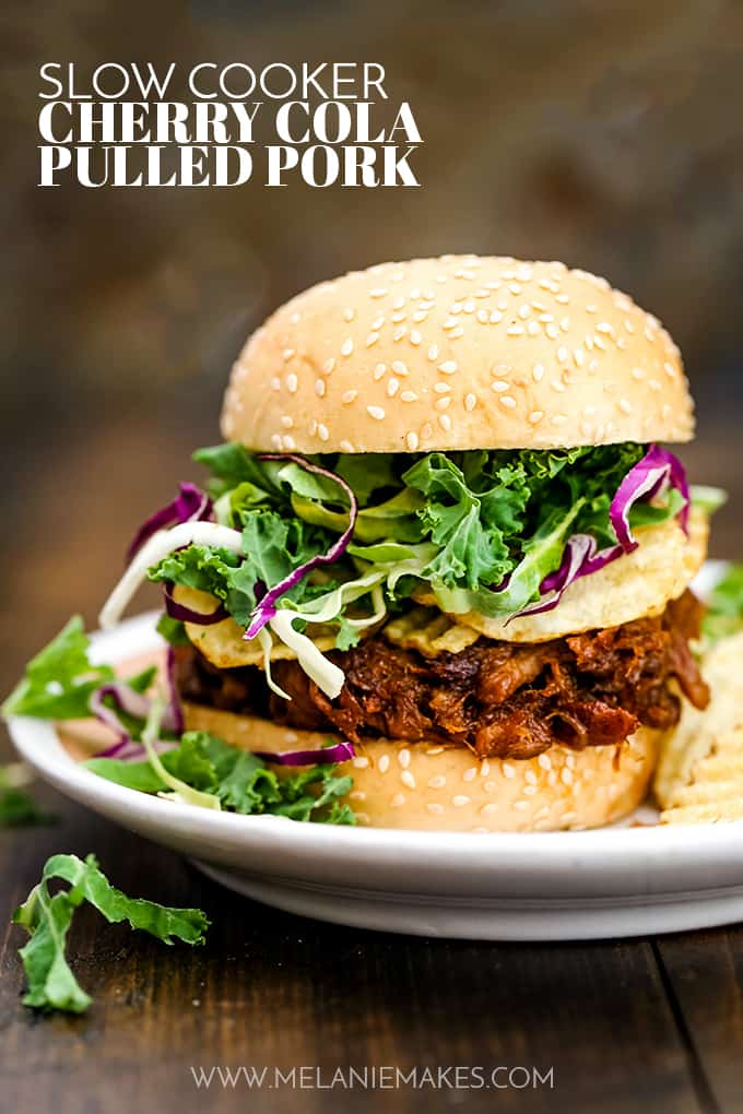 Slow Cooker Cherry Cola Pulled Pork is placed between two buns with cole slaw mix and potato chips.