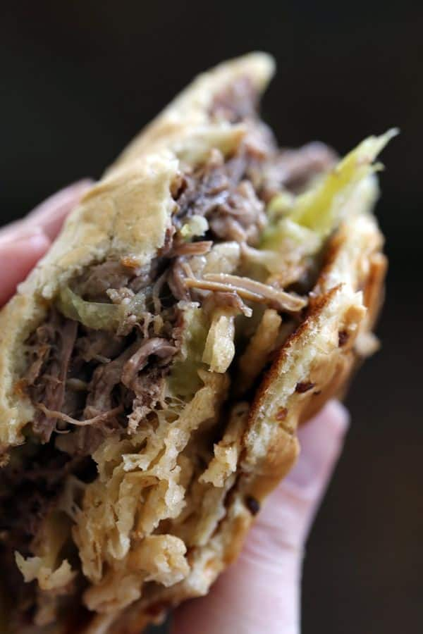 These five ingredient Slow Cooker Pepperoncini Beef Sandwiches are the easiest dinner recipe you've ever seen! With just 10 minutes prep, you'll soon have the perfect combination of succulent beef, melty cheese and crispy fried onions, all sandwiched between two pieces of bread!