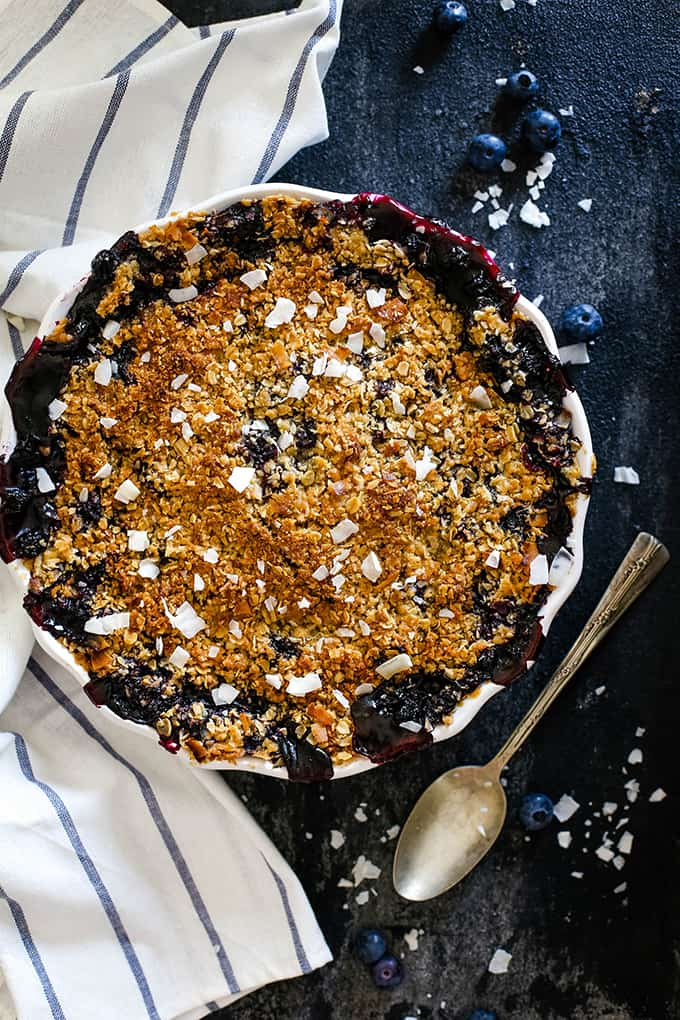 An overhead view of a Coconut Blueberry Crisp flanked by a striped napkin.