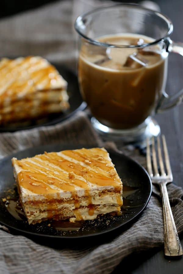 Layers of cinnamon graham crackers, caramel macchiato infused pudding and whipped topping create a rich and decadent No Bake Caramel Macchiato Cake that you can prepare in 10 minutes or less.  Cinnamon flecked vanilla frosting, a shower of graham cracker crumbs and a drizzle of caramel finish this delicious coffee inspired dessert.