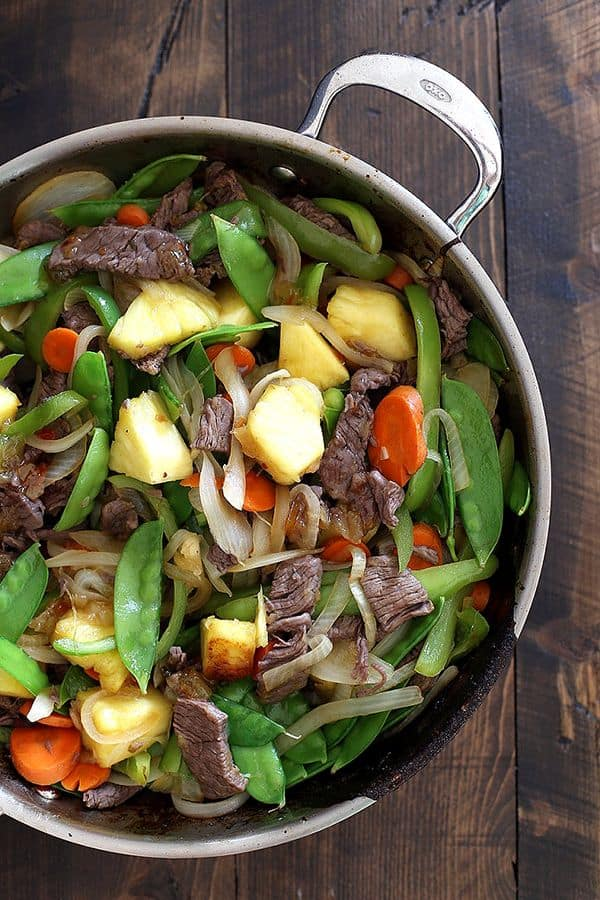 This eight ingredient Pineapple Beef Stir Fry is on the table in just 30 minutes making it perfect for busy weeknights. Sliced pieces of sirloin steak are stir fried with carrots, onions, green peppers, snow peas and pineapple to create a flavorful and colorful main dish.