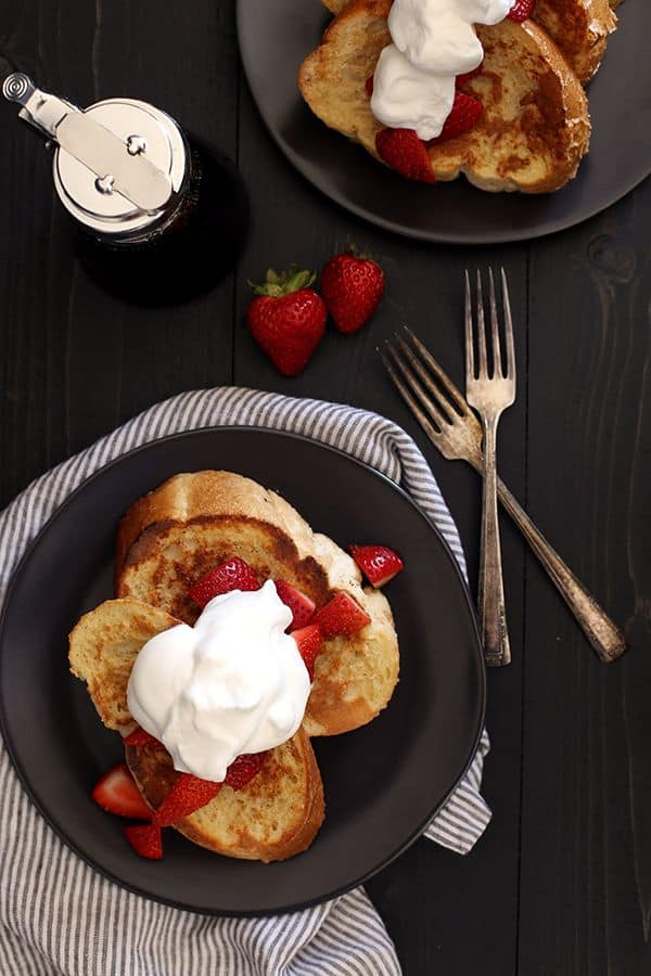 This Vanilla French Toast is guaranteed to become your new favorite breakfast. Thick slices of French bread are coated in an egg mixture spiked with both vanilla extract and vanilla paste and toasted until golden brown. Topped with whipped cream, maple syrup and fresh berries, every day should have such a delicious beginning!